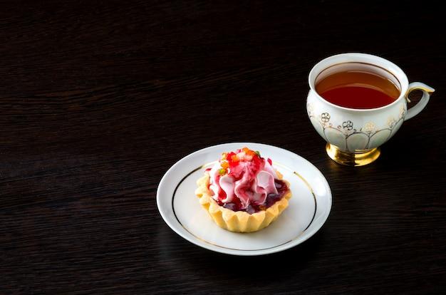 Cesta-bolo com geléia no prato e chá