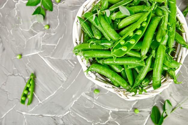Cesta branca com as ervilhas verdes frescas no fundo cinzento.