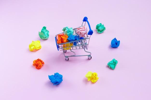 Cesta cheia com bolas de papel amassado e bolas coloridas espalhadas ao redor da cesta
