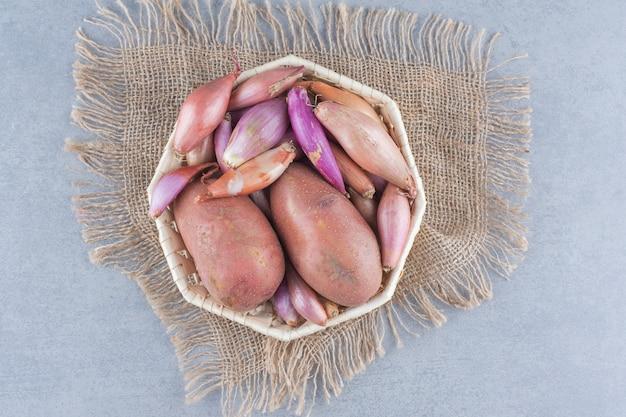 Cesta cheia de batatas e cebolas.