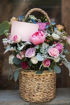 Cesta cheia de flores coloridas variadas e um cartão