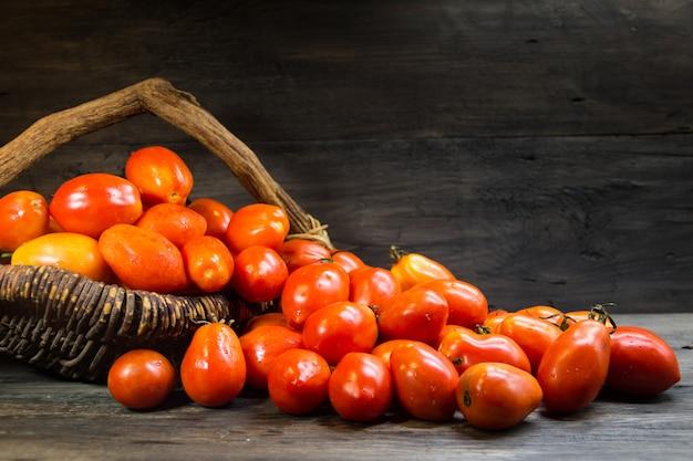 Cesta cheia de tomates pera em madeira rústica