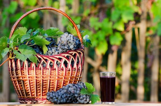 Cesta cheia de uvas maduras e um copo de suco no jardim