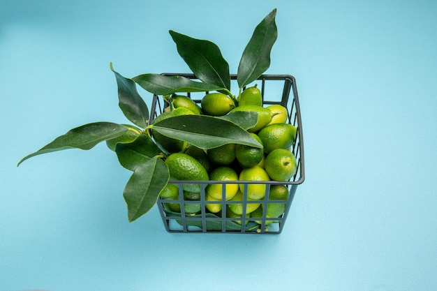 Cesta cinza de frutas cítricas vista lateral com frutas cítricas verdes e folhas na mesa azul