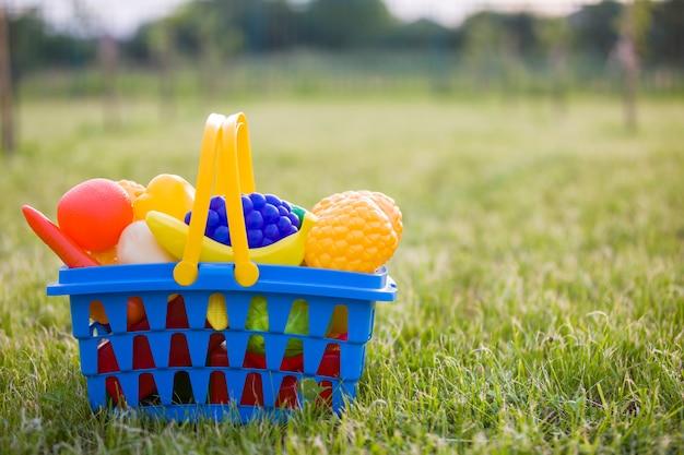 Cesta colorida plástica brilhante com frutas e legumes de brinquedo ao ar livre num dia de verão ensolarado.