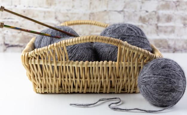 Cesta com bolas de lã e agulhas de tricô.