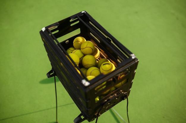 Cesta com bolas de tênis grandes, vista de cima, ninguém, cobertura verde da quadra. estilo de vida ativo e saudável, jogo de esporte com conceito de raquete
