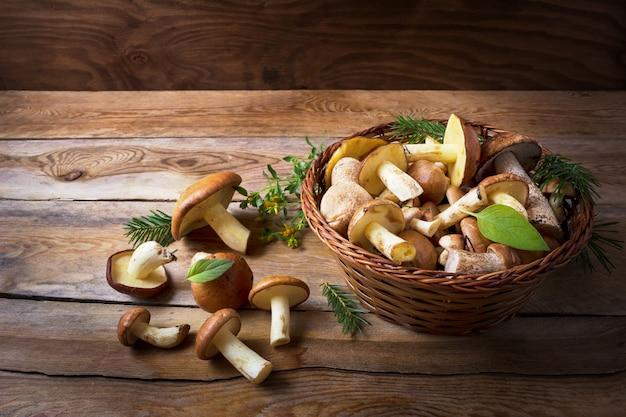 Cesta com cogumelos selvagens da floresta no fundo de madeira rústica