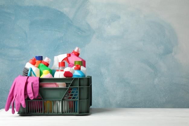 Cesta com detergente e material de limpeza na mesa de madeira, copie o espaço