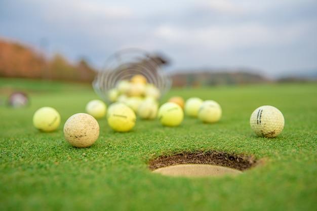 Cesta com equipamento de golfe no campo de golfe verde