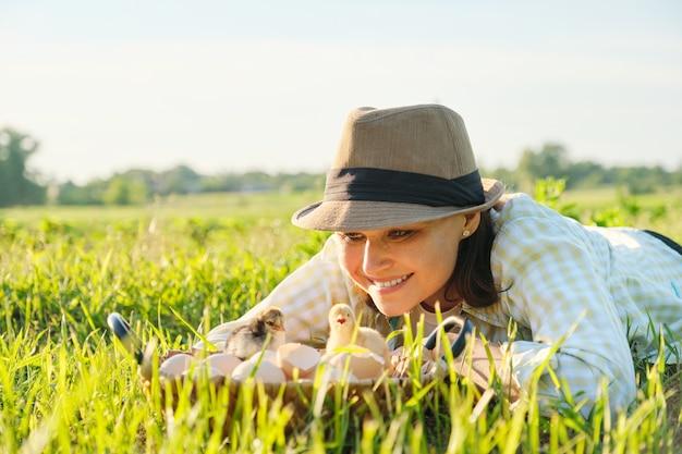 Cesta com galinhas recém-nascidas, mulher feliz com chapéu procurando pintinhos