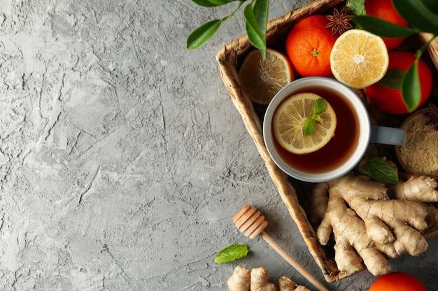 Cesta com gengibre, laranja, canela, limão e chá no fundo cinza