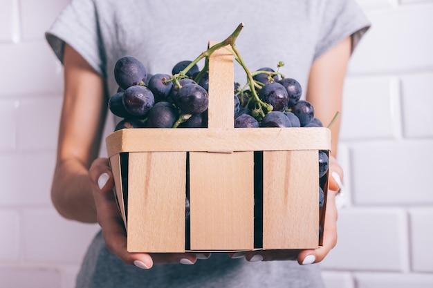 Cesta com grandes uvas azuis nas mãos femininas com manicure