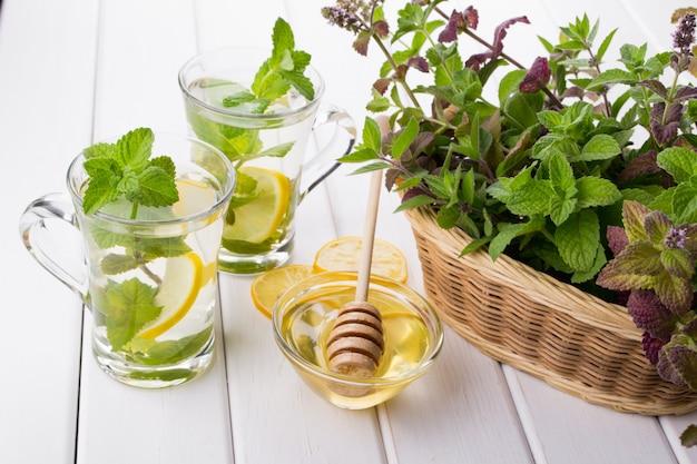 Cesta com hortelã verde fresca e dois copos de vidro com chá de hortelã fresca na mesa branca