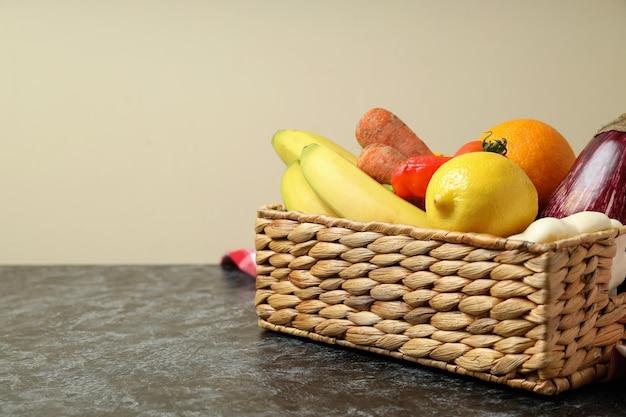 Cesta com legumes e frutas na toalha de cozinha na mesa esfumada preta