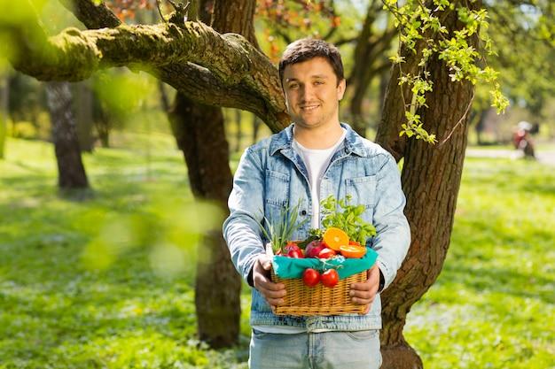 Cesta com legumes e frutas nas mãos de um fundo de agricultor da natureza