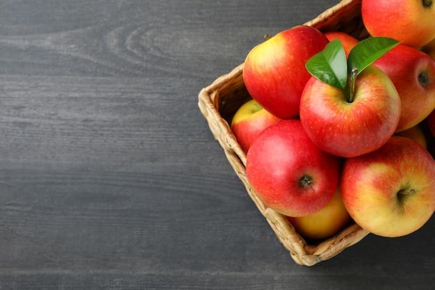 Cesta com maçãs vermelhas na mesa de madeira escura