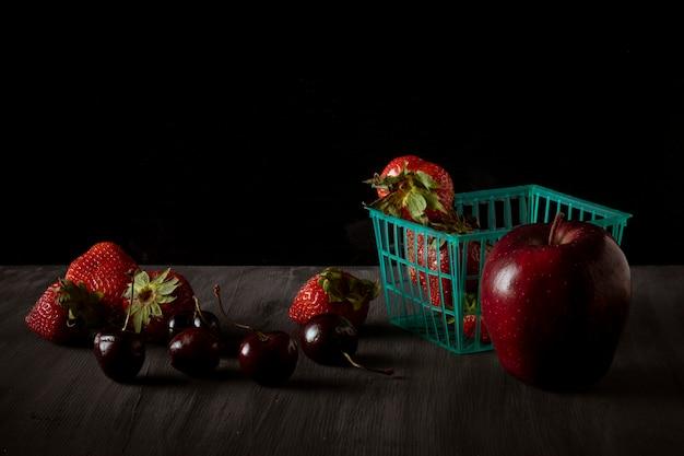 Cesta com morangos e uma maçã com cerejas ao lado em uma mesa de madeira vintage preta