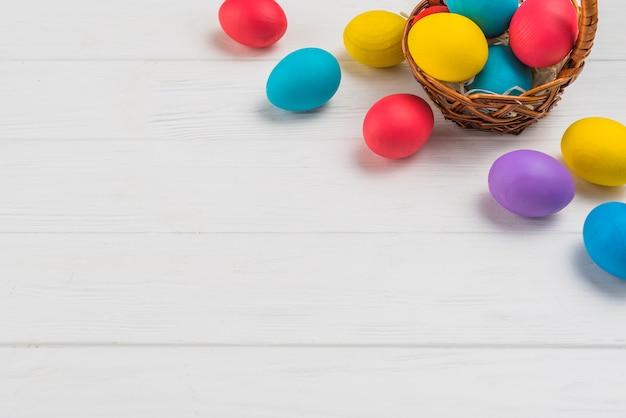Cesta com ovos de páscoa na mesa de madeira