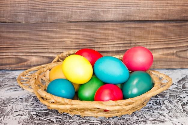 Cesta com ovos de páscoa no fundo de tábuas de madeira