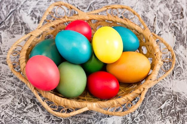 Cesta com ovos de páscoa no fundo de um fundo de concreto, conceito para o feriado da páscoa, férias de primavera