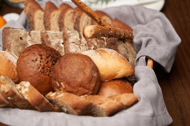 Cesta com pão fresco no fundo da mesa de madeira. variedade de produtos de panificação na cesta