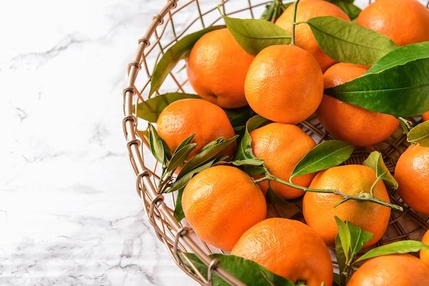 Cesta com saborosas tangerinas na mesa, closeup