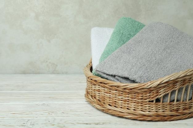 Cesta com toalhas limpas na mesa de madeira branca