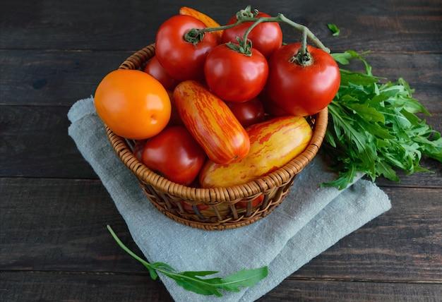 Cesta com tomates de diferentes variedades e molho de rúcula na superfície de madeira escura.