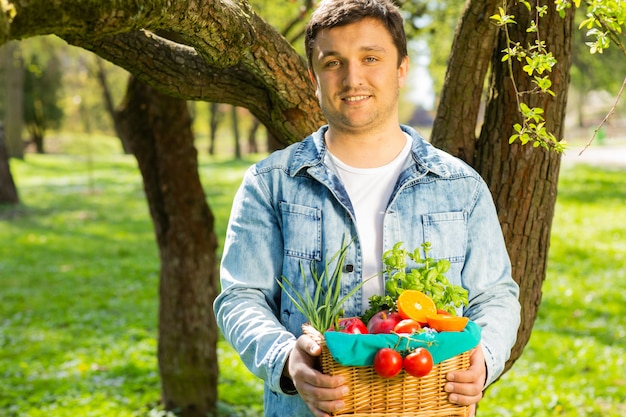 Cesta com vegetais e frutas nas mãos de um fundo do fazendeiro da natureza. de estilo de vida saudável