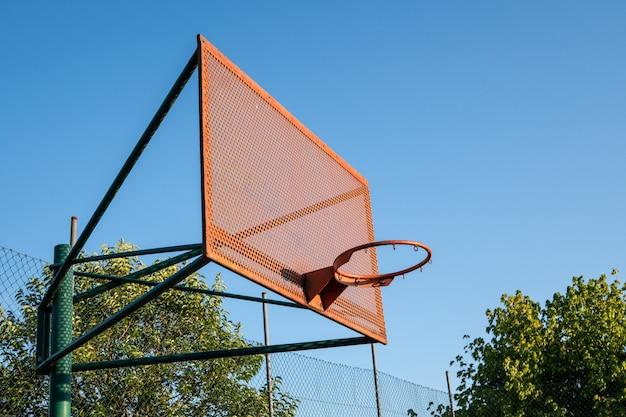Cesta de basquete ao ar livre com céu azul e árvores