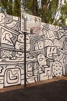 Cesta de basquete e tabela no fundo de uma parede pintada com graffiti e árvores
