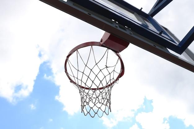 Cesta de basquete em uma quadra de basquete de rua sobre o céu azul nas nuvens