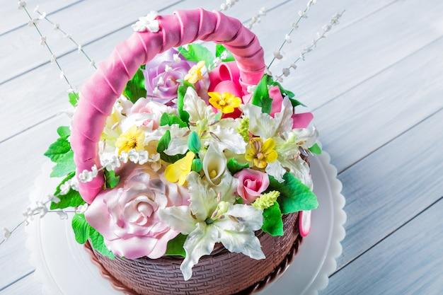 Cesta de bolo delicioso com várias flores na mesa de madeira branca