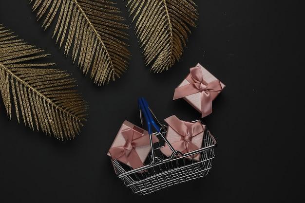 Cesta de compra com caixa de presente em fundo preto com folhas de palmeira douradas. moda plana lay. sexta-feira preta. vista do topo