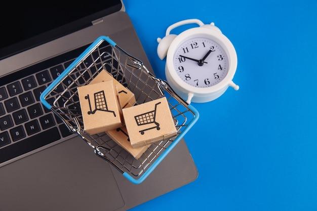 Cesta de compras, caixas e despertador em azul