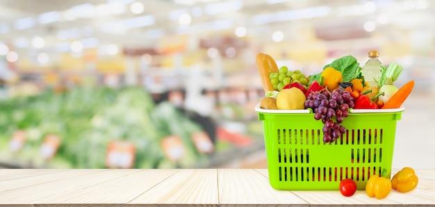 Cesta de compras cheia de frutas e vegetais na mesa de madeira com supermercado desfocado desfocado com luz bokeh