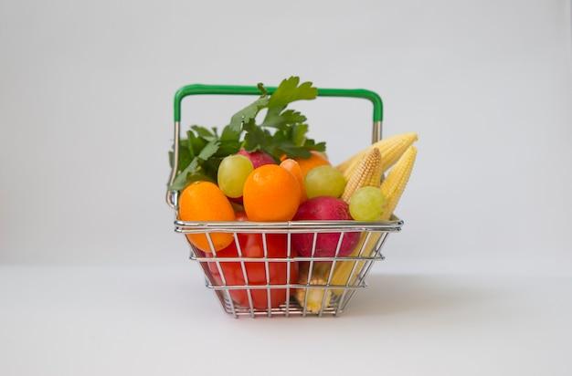 Cesta de compras cheia de mini frutas e vegetais
