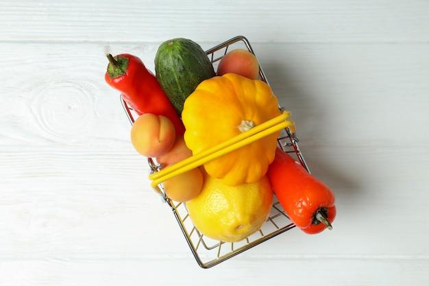 Cesta de compras com legumes e frutas na mesa de madeira