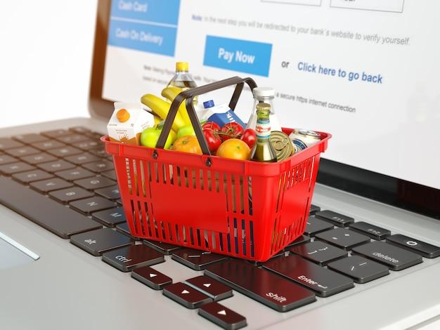 Cesta de compras com uma variedade de produtos de mercearia no teclado do laptop