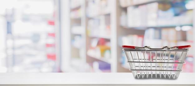 Cesta de compras vazia no balcão da farmácia da drogaria com um fundo desfocado de remédios e suplementos vitamínicos