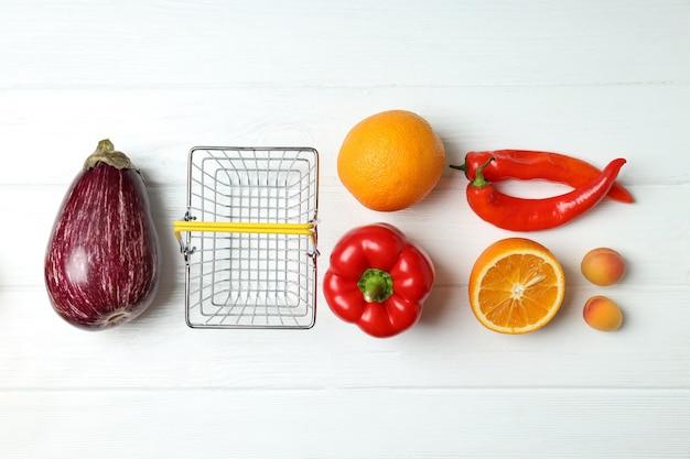 Cesta de compras, vegetais e frutas na mesa de madeira branca