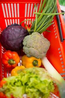 Cesta de cor vermelha com legumes e ervas na loja. pimenta, brócolis, cebola, salada, tomate, repolho.