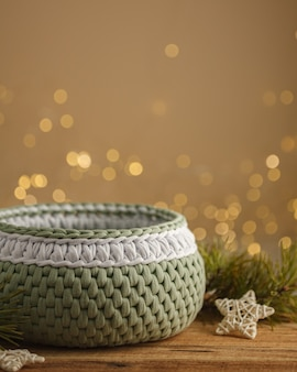 Cesta de crochê em um fundo de natal ramos de pinheiro, estrelas e bokeh de guirlandas em uma mesa de madeira. banco de fotografia
