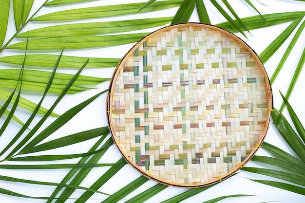 Cesta de debulha de bambu de madeira em folhas verdes