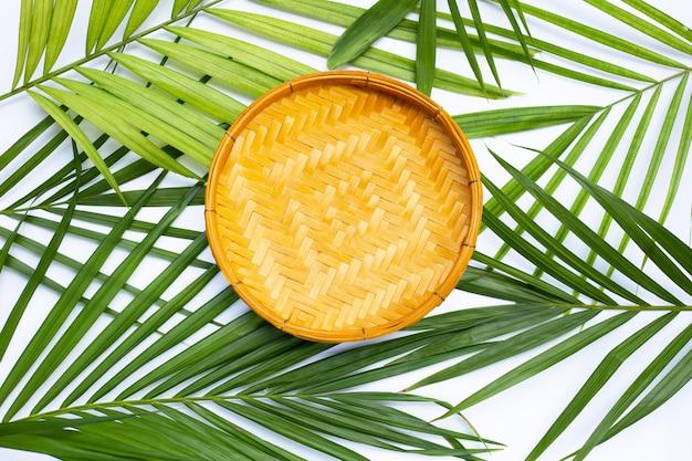 Cesta de debulha de bambu de madeira em fundo de folhas verdes.
