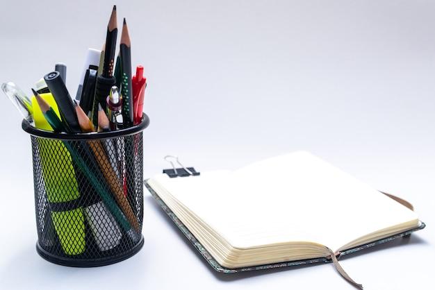 Cesta de escritório com lápis, canetas, marcadores e um caderno aberto