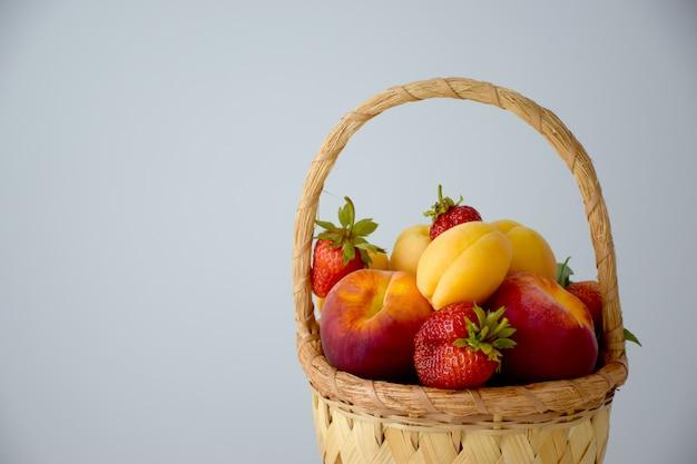 Cesta de fazenda cheia de várias frutas e bagas coloridas na mesa branca: pêssegos, morango e damasco