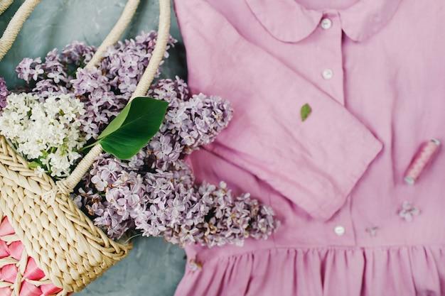 Cesta de flores lilases e vestido de verão rosa pastel