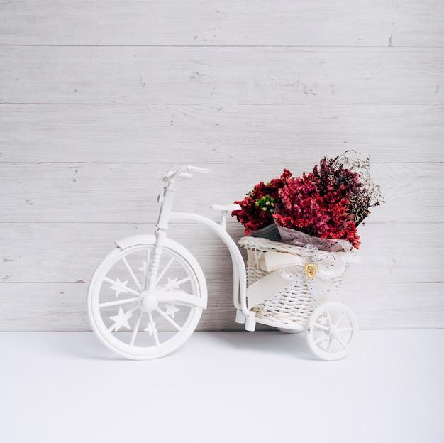 Cesta de flores na bicicleta branca na mesa contra a parede de madeira